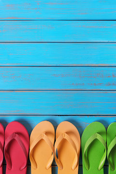 Flip flops in a row old weathered blue beach wood background vertical