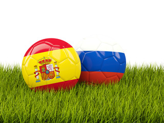 Spain vs Russia. Soccer concept. Footballs with flags on green grass