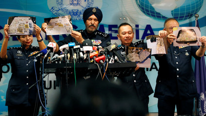 Commissioner Amar Singh, Malaysia's Federal Commercial Crime Investigation Department (CCID) director, and other police officers display photos of items from a raid during a news conference in Kuala Lumpur