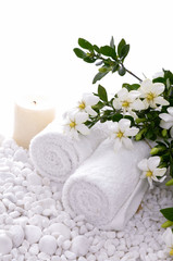 Rolled towel and candle and gardenia on white pebbles