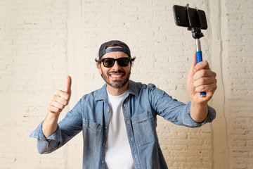 young attractive latin man taking a selfie with his smart cell phone.