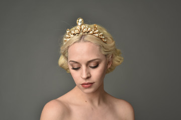 portrait of blonde woman wearing golden crown, grey studio background.
