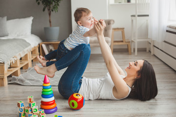 Young pretty mother playing with her little son. Cheerful family having fun indoors with little baby son