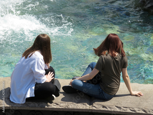 Two girls sitting near the fountain, rear view  Hot weather