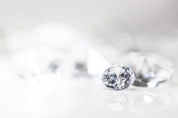 Diamant auf weiß mit Spiegelung vor weißem Hintergrund, mehrere Diamanten in der Unschärfe, Edelsteine mit Textfreiraum