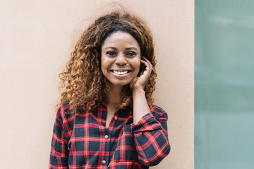 Young smiling black woman wearing checked shirt