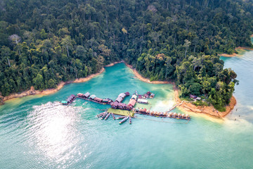 Drone aerial view beautiful landscape of mountains and bamboo huts on river natural attractions at Cheow Lan Lake, Khao Sok National Park in southern Thailand.