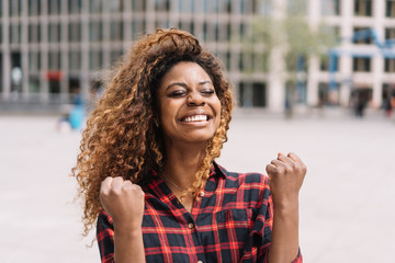 Excited young woman cheering and punching the air