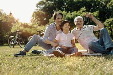 Relaxing together. Happy friendly united family sitting on the grass smiling and grandpa showing peace with his fingers while the boy taking selfies