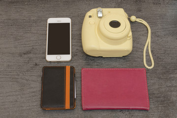 Yellow camera, smartphone, wallet and passport. Empty space. Top view