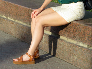 Sitting slim girl in a white short skirt and brown leather sandals. Naked legs, summer female fashion