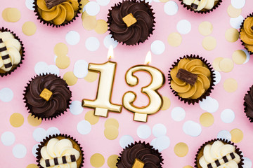 Number 13 gold candle with cupcakes against a pastel pink background