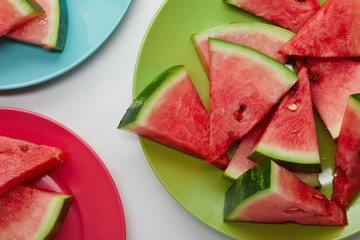flat lay with watermelon slices on colorful plates on white tabletop