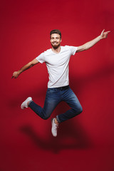 Full length portrait of a cheerful young bearded man