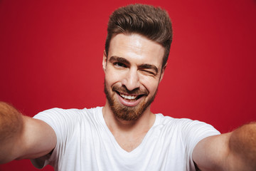 Portrait of a cheerful young bearded man winking