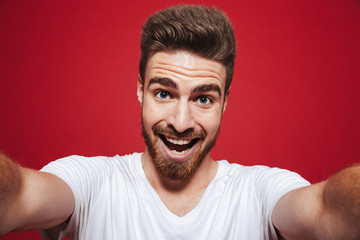 Portrait of a cheerful young bearded man taking a selfie