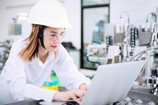 Female industrial engineer wearing hard hat uses laptop at factory.