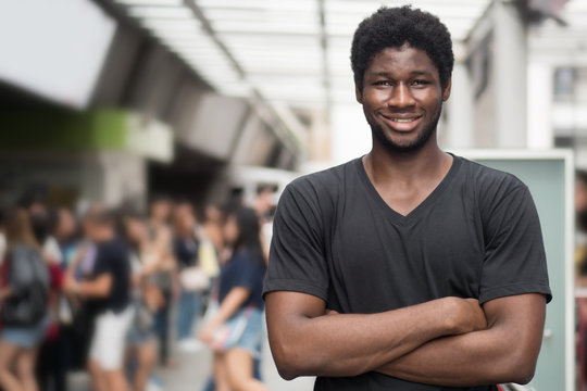 happy African man; portrait of happy smiling confident young adult black skin african man in casual outfit, urban city outdoor scene; west African young adult man model