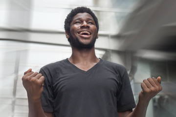 Strong successful African man portrait; happy smiling strong confident young adult african man expressing positive excited, surprised expression; African young adult man model