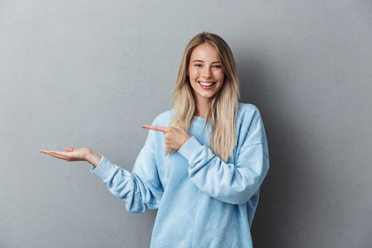 Portrait of a cheerful young girl in blue sweatshirt