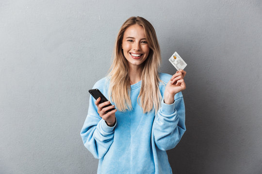 Happy young blonde girl in blue sweatshirt
