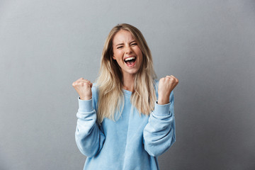 Portrait of a happy young blonde girl celebrating success Wall mural