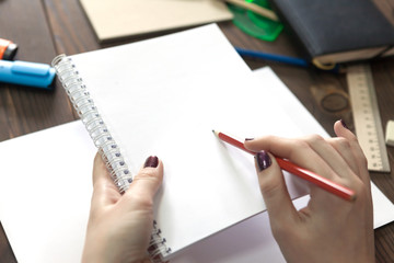 the girl draws a pencil in a notebook