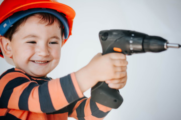 little builder in the helmet with a drill