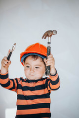 Little kid as a construction worker, hitting with a hammer