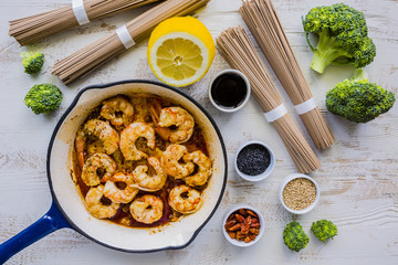 Ingredients for preparing teriyaki with shrimps with soba noodles and sesame seeds.