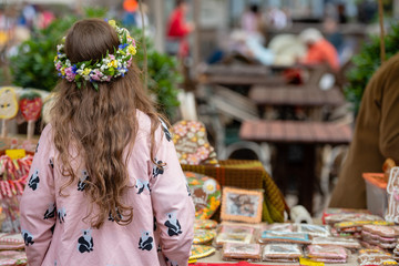 A girl with a crown of flowers looks forward. View from the back.