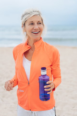 Blond woman exercising on a beach carrying water