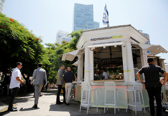 Britain's Prince William stands next to Tel Aviv's first kiosk founded in 1910, during a tour of Rothschild Boulevard, in Tel Aviv, Israel