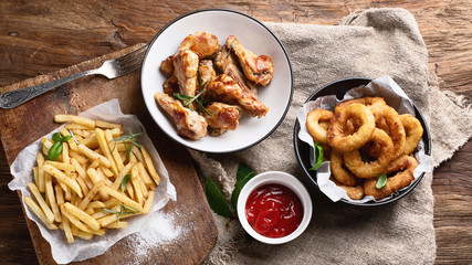 Fast food snacks - onion rings, fries and chicken wings