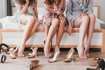 Cropped picture of caucasian fashion girls 20s wearing dresses trying on different summer shoes, during bachelorette party in cozy bedroom
