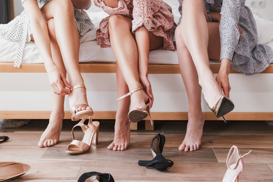 Cropped picture with legs of european girls 20s wearing dresses choosing and trying on summer stilettos, during bridal shower in apartment