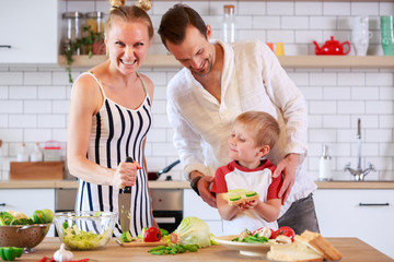 Image of parents and young son preparing food in kitchen