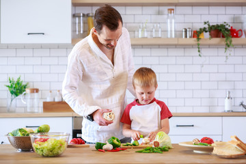 Photo of young father and son cooking at table with vegetables