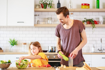 Photo of man with his daughter cooking dinner