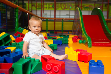 Little toddler child, playing in childrens playground indoors