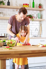 Image of father with little daughter cooking salad