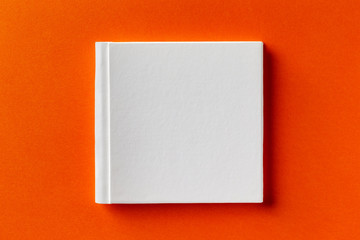 Mockup of square white closed book with leather cover isolated at orange design paper background.