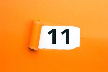 Zahl elf - 11 verdeckt unter aufgerissenem orangen Papier
