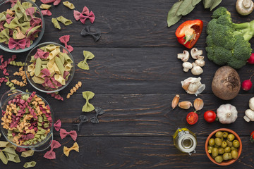 Assorted colorful pasta bowls on dark wood, top view