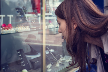 A young woman sees a store window with jewelry standing on the street.