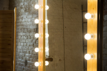 Close-up of a large mirror in a room with a brick wall