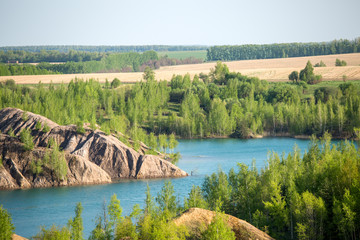 Photo of hilly terrain with green trees and river