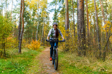 Photo of girl in helmet riding bike in autumn