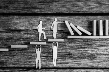 Greyscale image of small paper people holding up falling dominos while standing on wooden steps