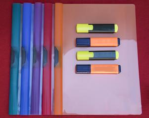 Carpetas de plástico y marcadores de colores.